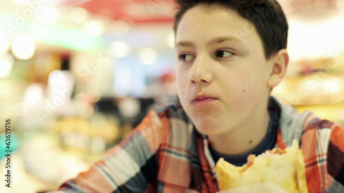 Young teenager eating sandwich in fast food restaurant