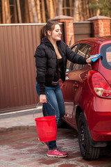 young woman washing her small red car