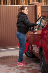 woman washing red car at yard of house