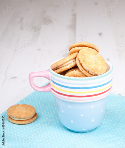 Cream cookies in a cup on the white wooden table
