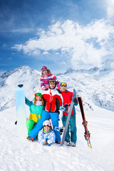 Smiling team with snowboards and skis