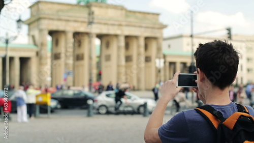 Young teenager taking photo with his smartphone of Brandenburg g