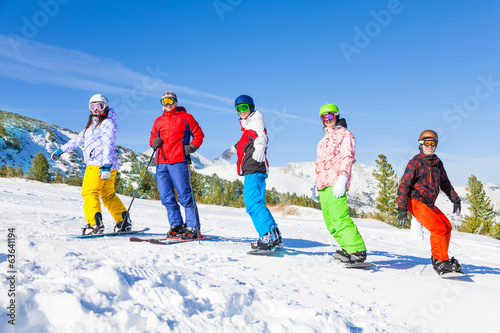 Skier and snowboarders standing in a row