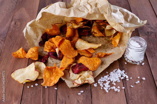 Healthy vegetable  chips on paper on a rustic wooden background
