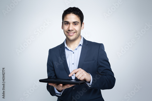 Smiling businessman working on a digital tablet against grey bac
