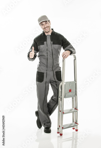 Full length portrait of a smiling worker in dungarees with a lad