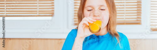Girl drinks orange juice indoors.