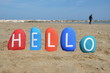 Hello on colourful stones and beach background