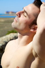 Closeup of handsome muscular man taking sunbath