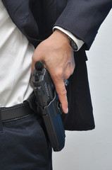 Agent wearing white shirt drawing gun from holster