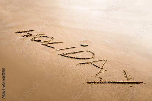 Holiday word written on the sand bright back light effect