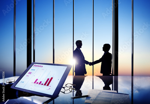 Silhouettes Of Two Businessmen Shaking Hands