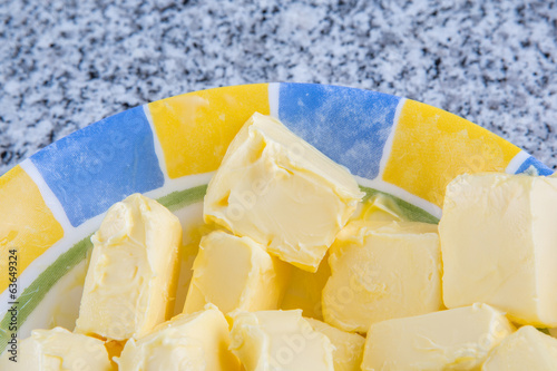 A group of melting butter in a bowl over granite surface