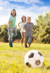 Happy couple with son playing with soccer ball