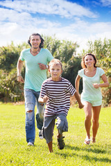 Happy family with  child  running  at  park
