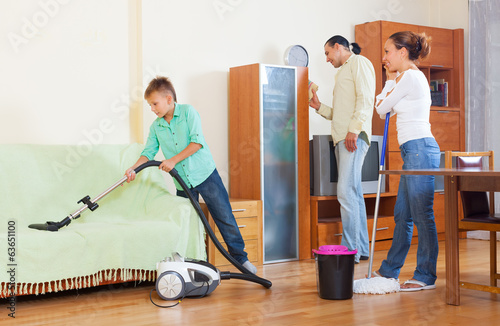 parents with  son doing house cleaning  in  home