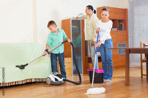 family of three doing housework