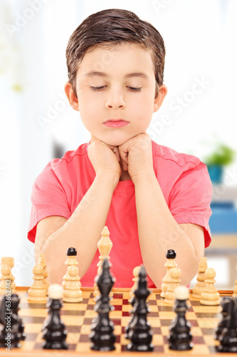 Focused boy playing chess seated at table indoors