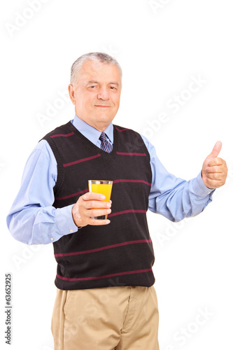 Mature man holding an orange juice and giving thumb up