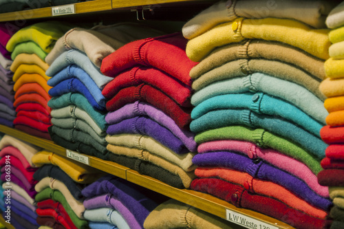 Piles of multi-colored cashmere products on shelves in the shop
