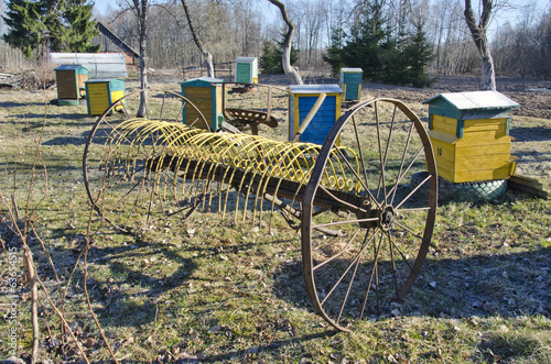 antique horse-drawn rake and beehive in farm garden