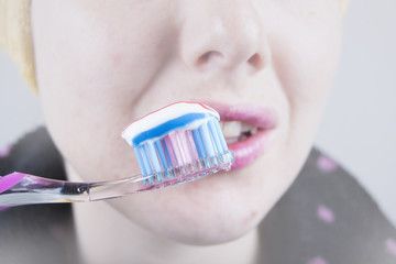 Woman brushing her teeth (brush, toothpaste)