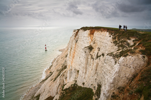 Walkers atop chalk cliffs at Beachy Head.