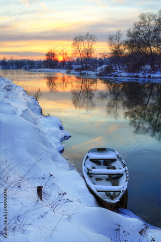 Winter sunset on the river with a boat