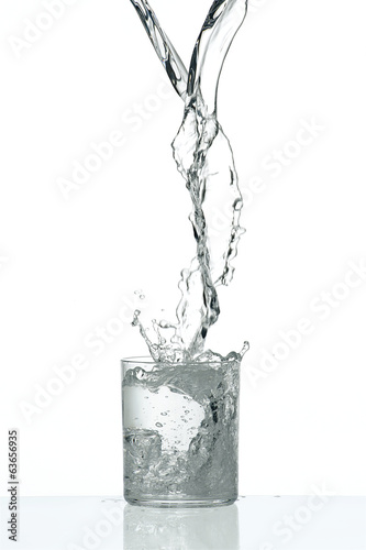 Fresh flow of water splashing in a tranparent glass