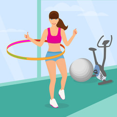 Beautiful woman exercising with hula hoop in the gym