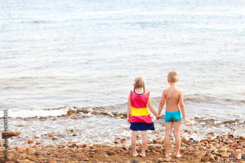 two children on the beach looking at sea