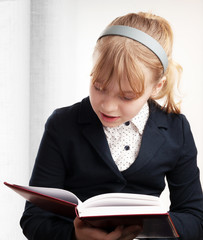 Рortrait of blond Caucasian schoolgirl with book