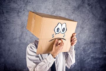 Businessman with cardboard box on his head and sad face expressi