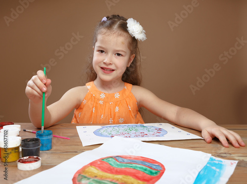 Little girl draws paints in kindergarten