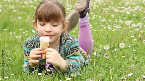 little girl lying on grass and eat ice cream