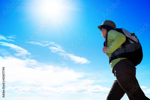 Female trekker agains blue sky.