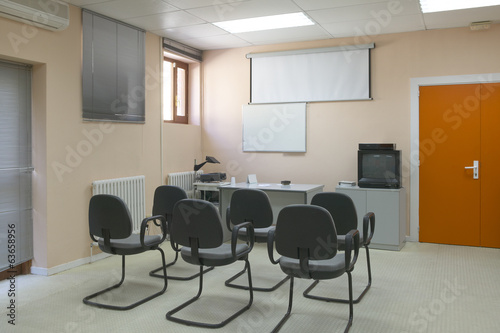 Classroom with projector, screen and board.
