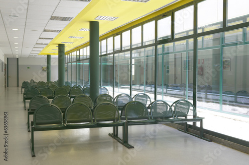 Waiting area with green chairs and windows.
