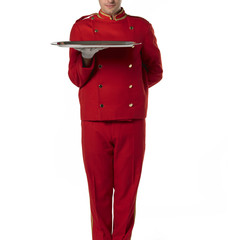 Bellboy with tray and red suit.