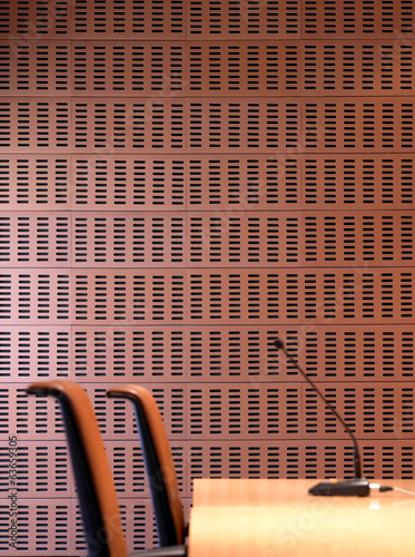 Interior ceramic wall detail with chairs and microphone.