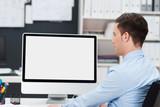 Fototapety geschäftsmann im büro schaut auf pc-monitor