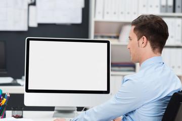 geschäftsmann im büro schaut auf pc-monitor