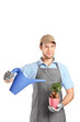 Man holding watering can and a plant