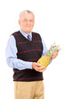 Mature man holding a pineapple