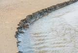 Disintegrating sand on the beach poster