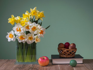 Daffodils in a vase of glass and easter eggs