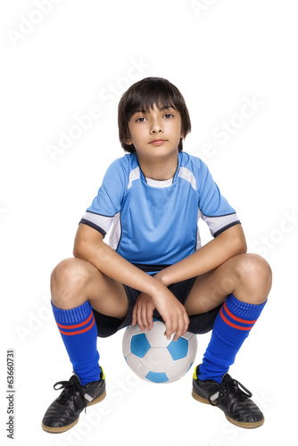 Boy in complete soccer outfit sitting on a football
