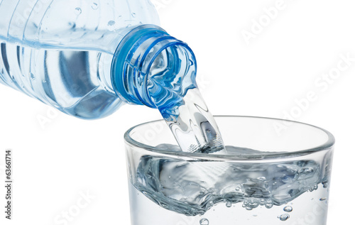 Pouring glass of water from a plastic bottle isolated on white b