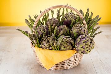 Cestino di vimini con carciofi ed asparagi  su un tavolo