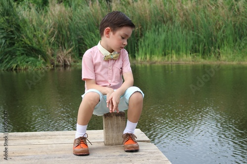 vintage lonely boy sitting by water